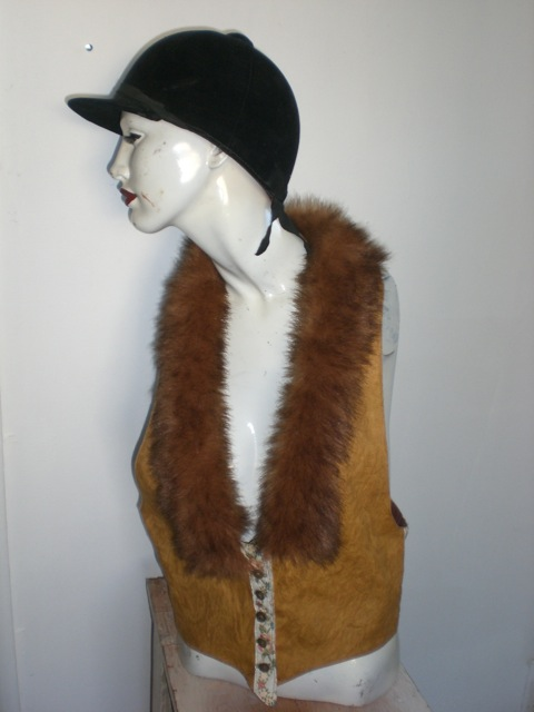 This brown vest is Liz's third try at a vest.  It is made from a table cloth, an embroidered belt and a monkey costume. The inside seams finally made it inside the lining.
